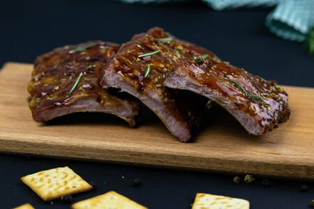 Barbecue Pork Spare Ribs as side view with basil and tomatoes and hot pepper with cracker on an old cutting board front views
