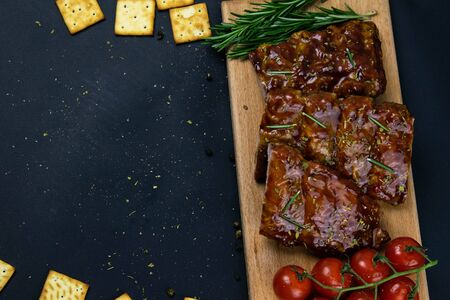 Barbecue Pork Spare Ribs as side view with basil and tomatoes and hot pepper with cracker on an old cutting board top views clear space