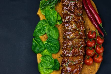 Barbecue Pork Spare Ribs close-up with tomatoes and basil as top view on an old cutting board top views