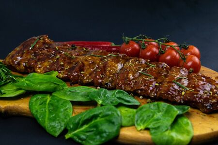 Barbecue Pork Spare Ribs as side view with basil and tomatoes on an old cutting board top views 写真素材