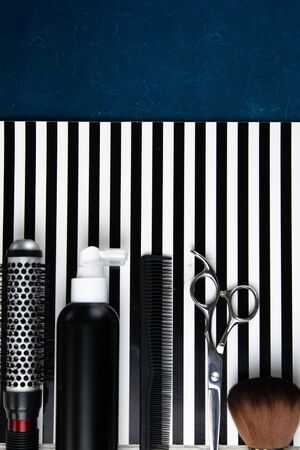 Haircut machines, nozzles of different sizes, combs and gels for styling, laid out on a beautiful black white striped background which stands on a blue background. Clear space