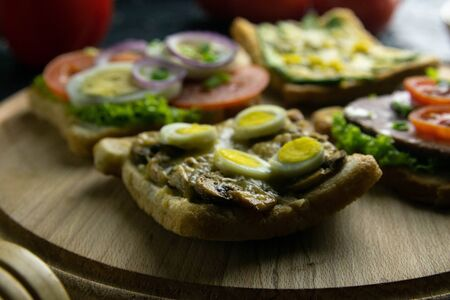Combination with different kinds of sandwiches on the wooden board: with mushrooms, with avocado and eggs, with ham lettuce and tomatoes, with avocado and seeds. Top views