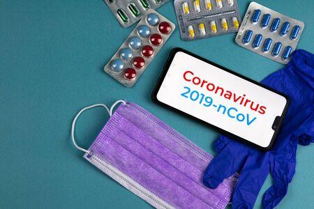 Coronavirus 2019-nCoV. Corona virus outbreaking. Epidemic virus Respiratory Syndrome. Mask, tablets and gloves, With a phone that says coronavirus 2019 nCoV