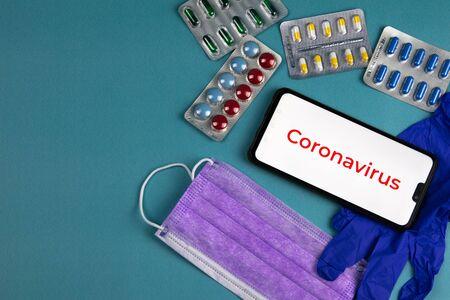 Coronavirus 2019-nCoV. Corona virus outbreaking. Epidemic virus Respiratory Syndrome. Mask, tablets and gloves, With a phone that says coronavirus