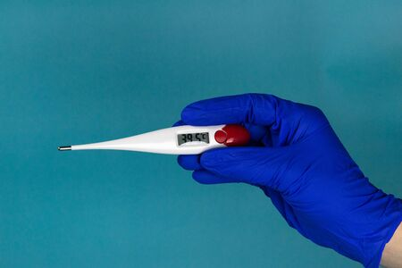 Coronavirus 2019-nCoV. Corona virus outbreaking. Epidemic virus Respiratory Syndrome. Hand with a Thermometer, a thermometer shows a temperature of 39.5 Celsius