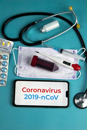 Coronavirus 2019-nCoV. Corona virus outbreaking. Epidemic virus Respiratory Syndrome.Blood tube, Phonendoscope, Mask, syringe, tablets and gloves With a phone that says coronavirus 2019 nCoV
