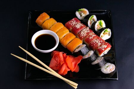 Black plate with sushi, filled with rolls of different kinds, next to stand sticks for sushi, red marinaginger and soy sauce on a black background. Front views
