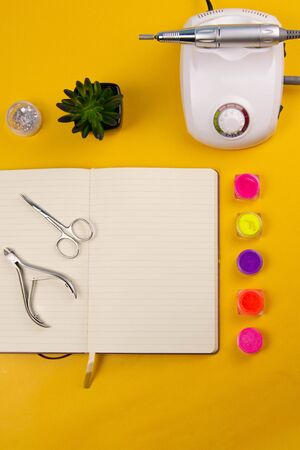 Set of cosmetic tools for manicure and pedicure on an orange background. Nearby there is an open notebook for writing, gel varnishes, a mill, nail files, scissors and nippers. Top views with clear space