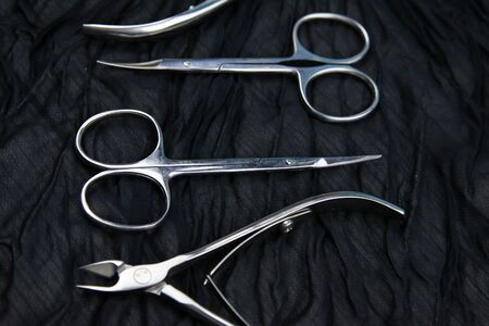 A set of cosmetic tools for manicure and pedicure stand on a black background. scissors and tongs. Top views