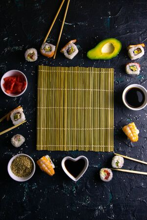 Different roles, avocado, red marinated ginger, rice, soy sauce are laid out on the perimeter in the shape of a square inside sushi mat. Top views with clear space
