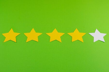 Rating concept. 5 stars from which 1 white - four yellow. Grade four. Everything stands on a green background. 版權商用圖片