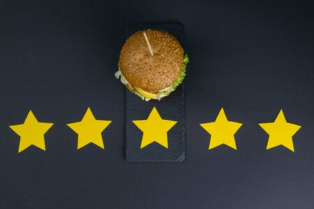 Burger isolated on a black background with a rating of 5 stars. Yellow stars. Top views Stock Photo
