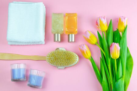 Three towels, body care oils and a tulips stand on a pinc background. The concept of spa treatments, a healthy body.