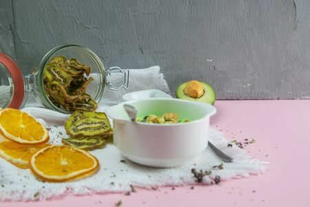 Curd with avocado and kiwi. Healthy eating concept. Assortment of products in bowls on pink background.