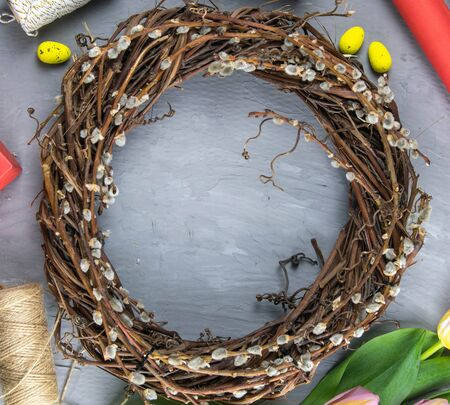 Easter wreath, yellow Easter eggs around tulips, gifts and wrapping paper. Top views with clear space