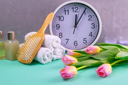 Three towels with a branch and a beautiful white clock and tulips on a turquoise background. Concept, time to prepare for spa treatments. Body health.