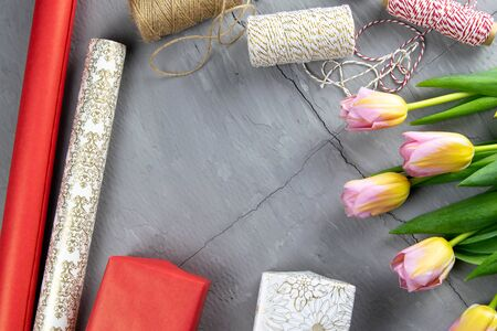 Preparing for the packaging of gifts, on the table laid out red and white wrapping paper, threads of different colors for winding, scissors and tulips.