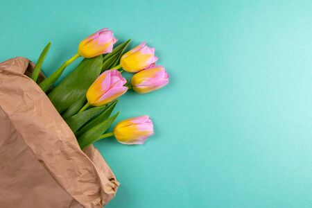 Bouquet of yellow tulip flowers in brown paper bag on mint background.
