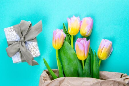 Bouquet of yellow tulip flowers in brown paper bag with gift on mint background.