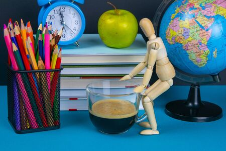 A stack of books with a globe, a glass of pencils, a clock apples and coffee. Zdjęcie Seryjne