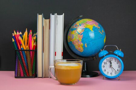 Coffe is in the foreground and behind him are a stack of books, a globe, a clock and a glass of pencils. Zdjęcie Seryjne