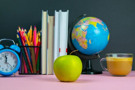 Apple is in the foreground and behind him are a stack of books, a globe, a clock and a glass of pencils.