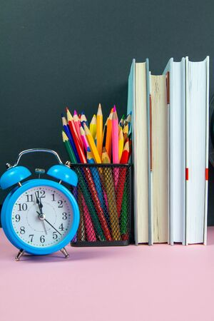 A stack of books, a clock and a glass with multi-colored pencils.