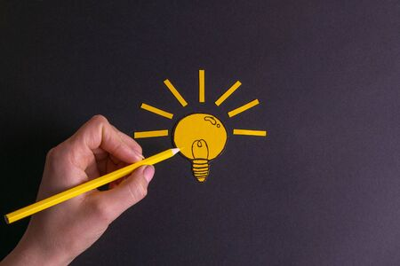 A yellow pencil in hand next to a creative painted light bulb. The concept of innovation and creative ideas