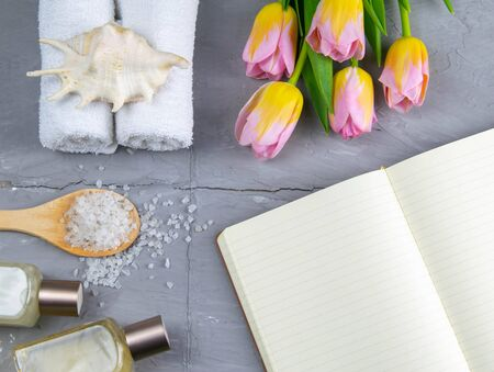 Spa with natural olive soap, tulips and sea salt and an open notebook for writing. Stock Photo
