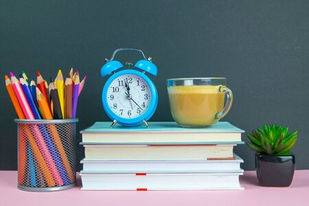 A stack of books on which stands a coffe with milk next to stands a green flower and a glass with pencils.