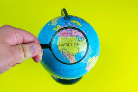 Close-up of a hand holding a magnifying glass to look at the globe in the library selective focus United States.