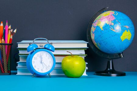 A stack of books with a globe, a glass of pencils, a clock and apples. Zdjęcie Seryjne