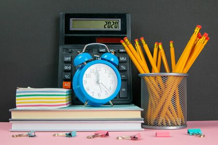 On a stack of books there is a calculator, a clock and sheets for notes, and next to a glass of pencils. Zdjęcie Seryjne