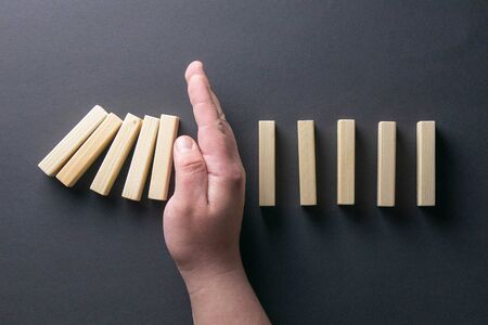 Top view man hand stopping falling dominos in a business crisis management conceptual image. Stock Photo