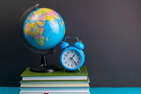 The globe and clock stand on a stack of books, on a blue table.