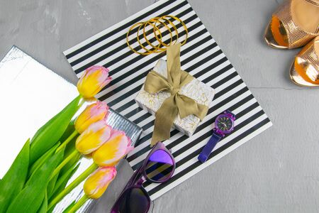 Tulips with a gift on a striped background along with glasses and watches.