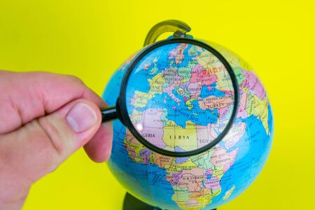 Close-up of a hand holding a magnifying glass to look at the globe in the library selective focus Europe.