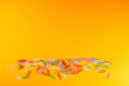 A pile of colored paper clips scattered on a orange surface. Standard-Bild