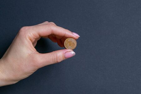 Hand sign by holding a coin, isolated on black background.