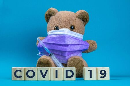 Covid 19. Coronavirus. Big teddy bear are sitting in blue medical masks on a blue background, concept of protection from respiratory disease, virus, and individual respiratory protection.