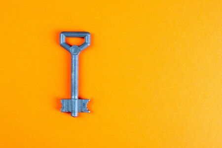 Metal old key on an orange background. Top views with clear space Imagens