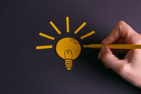A yellow pencil in hand next to a creative painted light bulb. The concept of innovation and creative ideas.