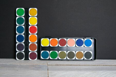 Colorful paints stand on a wooden table propped up against a black wall. Frontal view. 版權商用圖片