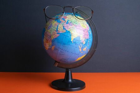 Glasses clad on the globe which stands on an orange background. Standard-Bild - 143293373