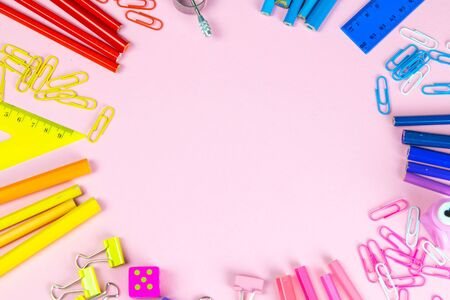Multi-colored pencils rulers, pens, pencils and scissors and stationery stand on a pink background.