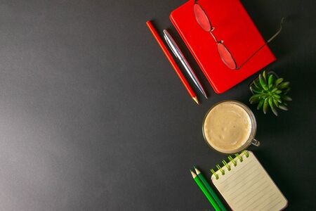The red notebook stands on a black background, on the notebook there are glasses and next to the notebook, a flower, coffe, pen and a red pencil.