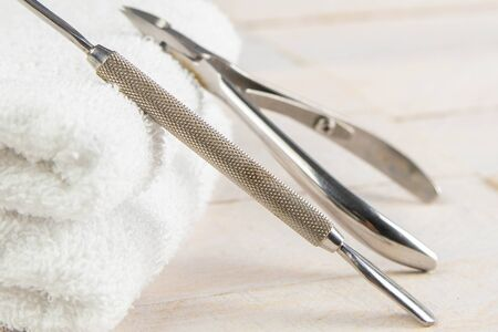 A set of cosmetic tools for manicure and pedicure on a blue background. A busher and cuticle cutters propped up to a white towel that stands on a white wooden table.