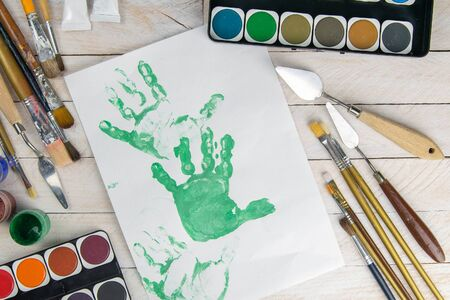Set of artist accessories collection. Canvas, tube of oil paint, art brushes, palette knife and a letter with a print of children's hands in green paint lying on the wood table. Artist workshop background.