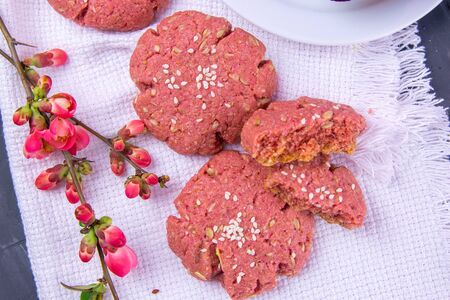 Beetroot oatmeal cookie stands on a white towel, next to a flowering branch with rose flowers. Top views, close-up.
