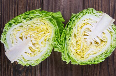 Ripe white cabbage on a wooden table. Top views, close-up.